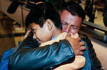 David Xol-Cholom, of Guatemala hugs his son Byron at Los Angeles International Airport as they reunite after being separated about one and half year ago during the Trump administration's wide-scale separation of immigrant families, Jan. 22, 2020.