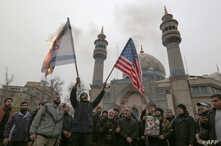 Iranians burn an Israeli and a U.S. flag during an anti-U.S. protest in the capital Tehran, Jan. 4, 2020, over the killings of Iranian military commander Qasem Soleimani and Iraqi paramilitary chief Abu Mahdi al-Muhandis.