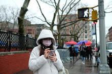 A woman wearing a face mask looks at her phone in Chinatown in the Manhattan borough of New York City, Jan. 25, 2020.