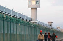 Workers walk by the perimeter fence of what is officially known as a vocational skills education centre in Dabancheng in…