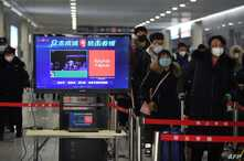Travelers pass through a fever detection system developed by Chinese search engine Baidu, at the Qinghe railway station, in Beijing, China, Feb. 6, 2020.