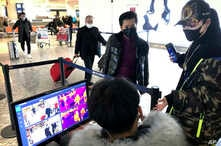 FILE - Travelers pass through a health screening checkpoint at Wuhan Tianhe International Airport, in Wuhan, in southern China's Hubei province, Jan. 21, 2020.