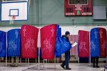 A man walks out of a voting booth during the New Hampshire Primary in Manchester, N.H., Feb. 11, 2020.