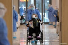 FILE - A medical worker in a protective suit moves a coronavirus patient in a wheelchair at a hospital in Wuhan, Hubei province, China, Feb. 10, 2020.