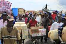 FILE - People carry items into Haiti from the Dominican Republic in Malpasse, Haiti, April 1, 2010.