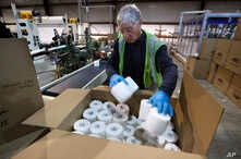 Scott Mitchell fills a box with toilet paper at the Tissue Plus factory, Wednesday, March 18, 2020, in Bangor, Maine. The new company has been unexpectedly busy because of the shortage of toilet paper brought on by hoarders concerned about the coronavirus.