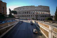 An empty street leads to the ancient Colosseum, in Rome, March 24, 2020.