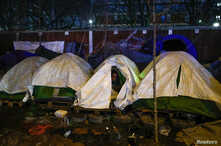 A migrant sits in his tent during the evacuation of a makeshift camp set up near the La Porte d'Aubervilliers in Paris, France,…