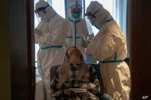 A woman takes a COVID-19 test at a quarantine hotel in Wuhan in central China's Hubei province, March 31, 2020.