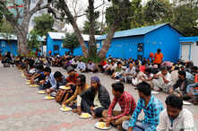 Daily wage workers and homeless people eat food inside a government-run night shelter during a 21-day nationwide lockdown to limit the spreading of coronavirus disease (COVID-19), in the old quarters of Delhi, India, March 26, 2020.