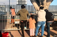 In this Wednesday, Jan. 8, 2020, photo, people seeking asylum in the United States wait at the Mexico border crossing
