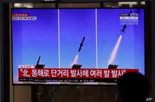 People watch a TV screen airing reports about North Korea's firing missiles with file images of missiles at the Seoul Railway…