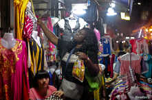 """FILE - An African woman shops at a market at """"African village"""" in Guangzhou, Guangdong province, October 25, 2014."""