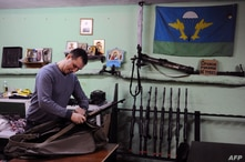 """FILE - A member of the Russian Imperial Movement, a nationalist group in Russia, Denis Gariyev - nick-named """"Instructor"""" - holds a weapon simulator at a training base in Saint-Petersburg, Feb. 28, 2015."""