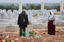 A woman reacts at a grave of her daughter, an SDF fighter killed during fightings with Islamic State militants, at a cemetery…