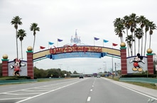 FILE - In this Monday, March 16, 2020, file photo, the road to the entrance of Walt Disney World has few cars, in Lake Buena…