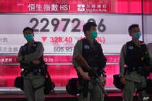 Riot police wearing face mask stand guard in front of a bank electronic board showing the Hong Kong share index at Hong Kong…