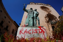 "A graffiti reading ""racist"" is seen on a statue of Fray Junipero Serra in Palma de Mallorca, Spain, June 22, 2020."