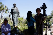 File - In this Sept. 23, 2015 file photo, an interview is conducted next to a statue of Junipero Serra at the Carmel Mission in…
