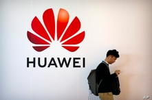 FILE - In this Oct. 31, 2019, filer photo, a man uses his smartphone as he stands near a billboard for Chinese technology firm…