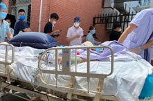 A patient on a hospital bed is pushed past a line of residents waiting to be tested at a fever clinic in Beijing, China, June 15, 2020.