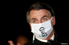 FILE - Brazil's President Jair Bolsonaro speaks with journalists while wearing a protective face mask.