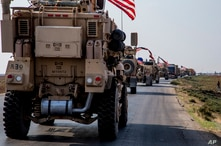 U.S. military convoy drives near the town of Qamishli, north Syria, Saturday, Oct. 26. 2019. A U.S. convoy of over a dozen…