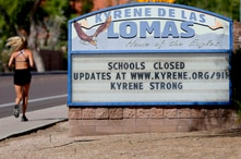 A runner passes a school closed sign in Phoenix.