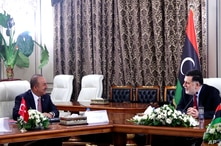 FILE - Turkey's Foreign Minister Mevlut Cavusoglu, right, and Fayez Sarraj, the head of Libya's internationally-recognized government, speak during a meeting in Tripoli, Libya, June 17, 2020.