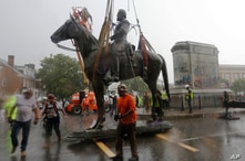 Workers remove the statue of Confederate General Stonewall Jackson from it's pedestal on Monument Avenue, July 1, 2020, in Richmond, Virginia.