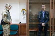 Ivan Safronov, an adviser to the director of Russia's state space corporation, stands in a cage in a courtroom in Moscow,…