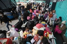 Venezuelan migrants wait for a bus in Bogota, Colombia, July 2, 2020, to travel to the border.