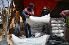 Workers carry the aid provided by the World Food Programme (WFP) for distribution in Pissila, Burkina Faso January 24, 2020…