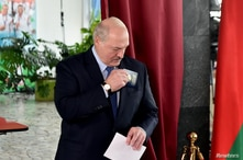 Belarusian President Alexander Lukashenko holds a ballot and a passport before casting his vote at a polling station during the…