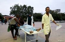 Paramedics and civilians carry an injured person on a stretcher at Madina hospital after a blast at the Elite Hotel in Lido…