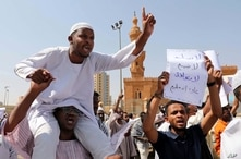 """A man holds a poster with Arabic that reads, """"we will not give up, we will not sell out, we will not agree on normalization,""""…"""