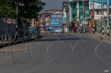 A barbwire blocks a deserted street on the first anniversary of India's decision to revoke the disputed region's semi-autonomy, in Srinagar, Indian controlled Kashmir, Aug. 5, 2020.