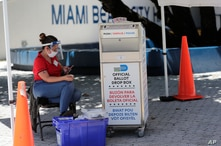 A poll worker wears personal protective equipment as she monitors a ballot drop box for mail-in ballots outside of a polling station during early voting, Aug. 7, 2020, in Miami Beach, Florida.