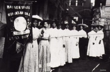 Black suffragists like Nannie Burroughs (holding a Woman's National Baptist Convention banner) called for Black and white women to cooperate to achieve the right to vote.