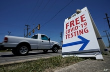 FILE - A pick-up truck passes a sign for free COVID-19 testing, in San Antonio, Texas, Aug. 14, 2020.