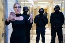 FILE - Opposition activist Lyubov Sobol reports live by phone as policemen stand guard during a raid at offices of the Anti-Corruption Foundation, in Moscow, Russia, Dec. 26, 2019. The foundation was established by prominent Kremlin critic Alexei Navalny.