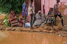 Sudanese residents sit outside their house at the flooded area of alqamayir in the capital's twin city of Omdurman, on August…