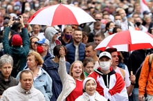 Opposition supporters carrying umbrellas in the colors of a former white-red-white fag of Belarus parade through the streets…