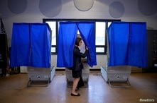 A voter leaves the booth after casting her ballot in the Pennsylvania primary at a polling place in Philadelphia.