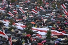 People take cover from rain under umbrellas during an opposition rally to protest against police brutality and to reject the presidential election results in Minsk, Belarus, Sept.r 6, 2020.