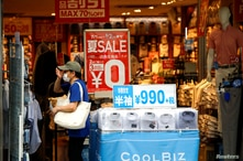 FILE - A shopper wearing a protective face mask is seen at a shop selling office wear, amid the coronavirus disease (COVID-19) outbreak in Tokyo, Japan, July 27, 2020.