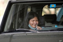 Ashley Ruiz gives herself a COVID-19 nasal swab test while sitting in a car at a drive-up CVS pharmacy in Dallas, Friday, Sept…