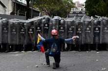 FILE - A man kneels in front of police blocking a march called by opposition leader Juan Guaido, in Caracas, Venezuela, March 10, 2020.