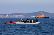 FILE - Migrants on a dinghy are approached by a Greek coast guard boat near the port of Thermi, as they crossed part of the Aegean Sea from Turkey to the island of Lesbos, Greece, March 1, 2020.