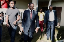 FILE - Maurice Kamto, a presidential candidate of Renaissance Movement (MRC), walks with his staff.